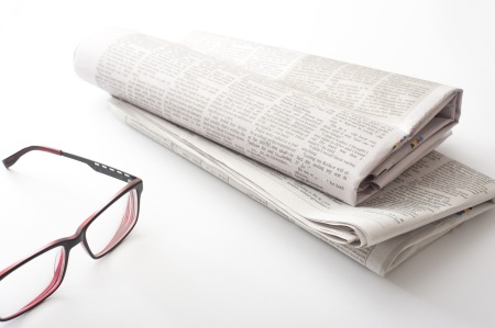 Folded newspaper with reading glasses on a white background with copy space conceptual of relaxation